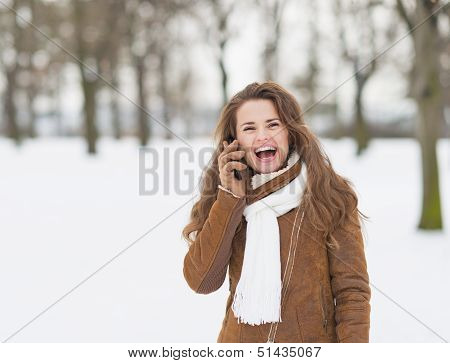 Smiling Young Woman In Winter Park Talking Cell Phone