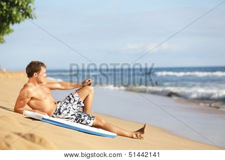 Beach man relaxing after surfing on beautiful beach. Handsome fit male model in swimming wear enjoying summer holidays vacation on Kaanapali beach, Maui, Hawaii, USA