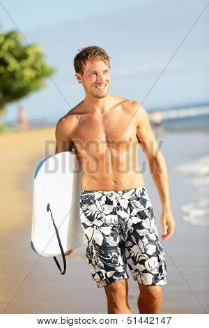 Man on beach holding body surfing bodyboard doing water sports. Summer vacation travel outdoor activity image with handsome fit male fitness sport model smiling happy on tropical beach. Hawaii, USA.