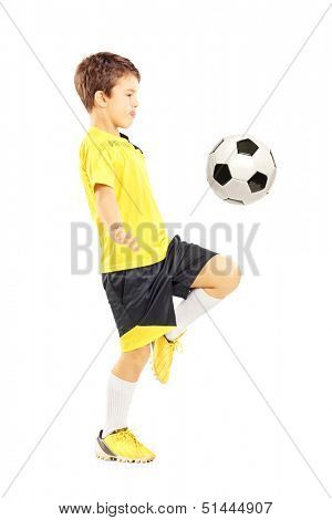Full length portrait of a child in sportswear joggling with a soccer ball isolated on white background
