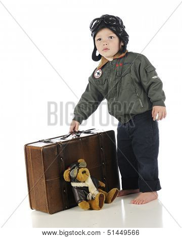 An adorable toddler in his old-time pilot outfit picking up his suitcase.  On a white background.