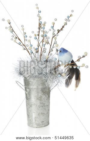 A feathery blue bird sitting on a branch of berries in a tall galvanized bucket.  On a white background.
