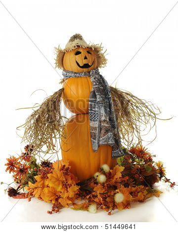 A snowman-style lady composed of 3 pumpkins.  She's wearing a straw hat, multi-colored scarf and has bushy arms and hands.  And she's surrounded by colorful fall foliage and leaves.