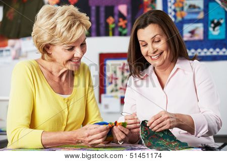 Two Women Sewing Quilt Together