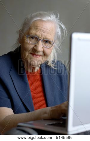 Elderly Woman Typing On Laptop