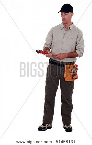 Amazed man holding a pipe wrench