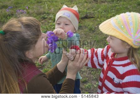 Two Happy Children Are Reaching Out To Its Mother Bunch Of Flowe