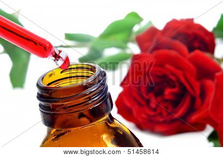 closeup of a dropper bottle with rose essence with red roses on the background