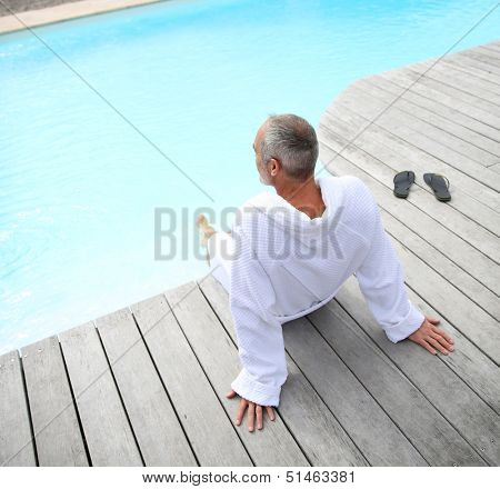Senior man with spa bathrobe relaxing by pool