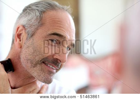 Senior man shaving beard with electric razor