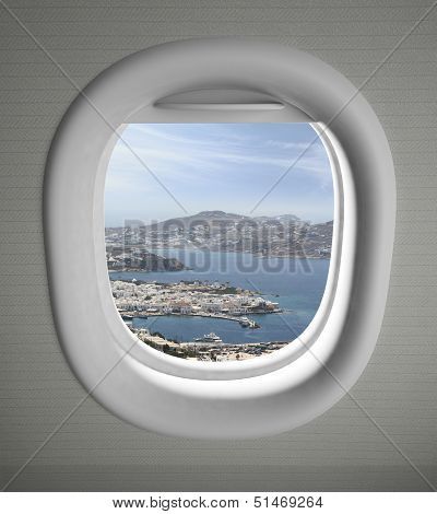 Airplanes window seat view with sea scape and some land