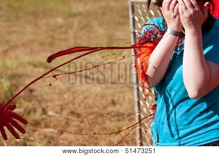 Female Zombie Gets Fake Blood Splattered On Her Clothes