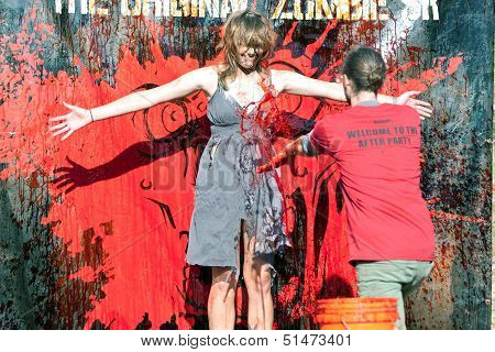 Female Zombie Gets Fake Blood Splattered On Her Dress