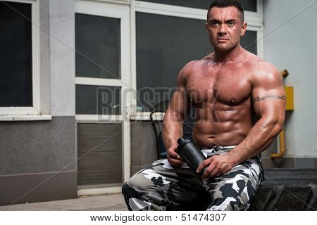 Bodybuilder Resting And Drinking Protein Shake After Exercising In Gym