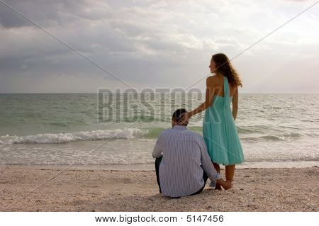 Beautiful Image Of Two Young Lovers At The Beach At Sunset Looking Out To The Ocean