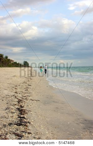 Lomg Distance Shot Of Couple Walking Beach