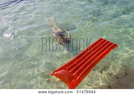 Woman Diving Under Water Towards A Lilo