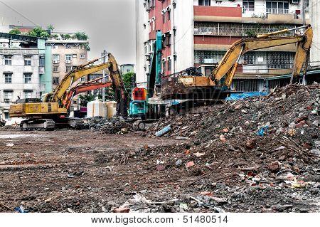 Earthmovers Demolishing Building