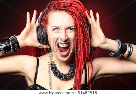 Expressive girl in headphones with great red dreadlocks.
