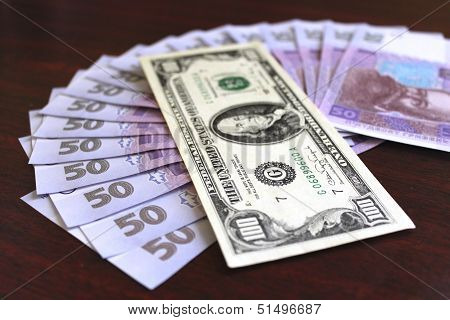 dollars and grivnas banknotes on dark background