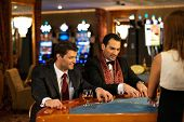 foto of roulette table  - Two young cheerful men behind table in a casino - JPG