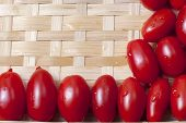 picture of oblong  - Small oblong red ripe tomatoes on a wicker wooden platter - JPG