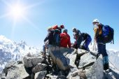 stock photo of mountain-climber  - Group alpinists accomplishing an ascent rests on the top mountains - JPG