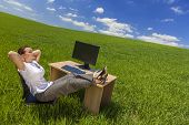 foto of field mouse  - Business concept beautiful woman sitting relaxing day dreaming at desk feet up with computer in a green field with bright blue sky  - JPG
