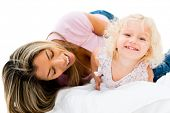 Happy mother tickling her daughter  - isolated over white background