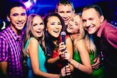 stock photo of singing  - Portrait of happy girls and guys singing in microphone in the karaoke bar - JPG