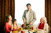 Portrait of happy family gathered by festive table on holiday evening