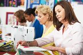 picture of thread-making  - Group Of Women Using Electric Sewing Machines In class - JPG