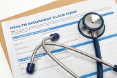 stock photo of reimbursement  - Medical reimbursement with health insurance claim form and stethoscope - JPG