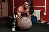 foto of strongman  - Muscular Man Trying To Pick Up A Stone Exercise - JPG
