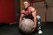 stock photo of strongman  - Muscular Man Trying To Pick Up A Stone Exercise - JPG