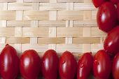 stock photo of oblong  - Small oblong red ripe tomatoes on a wicker wooden platter - JPG