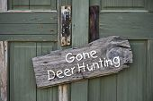 image of deer rack  - Gone deer hunting sign on old green door - JPG