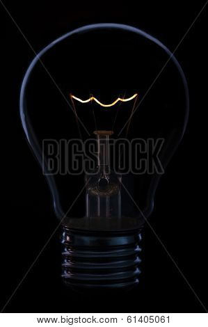 Glass Light Bulb With Burning Filament Upright With Black Background