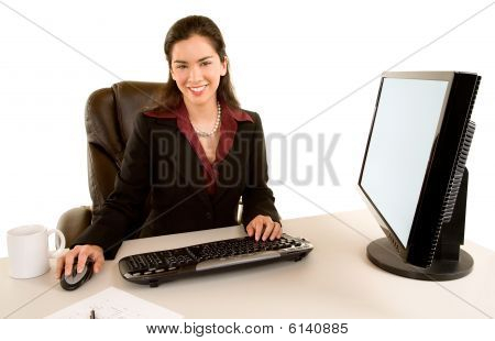 Businesswoman Sitting At Her Desk And Smiling At The Camera