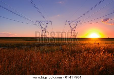 South African Electricity Power Lines With Sun At Dusk On The Highveld.