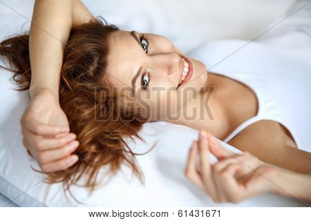 Joyful woman in bed