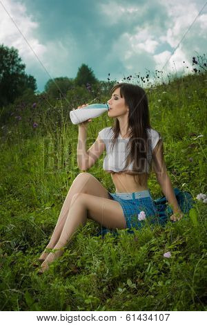 girl in a t-shirt drinking milk.