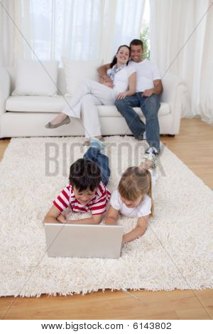 Brother And Sister Using A Laptop On Floor In Living-room