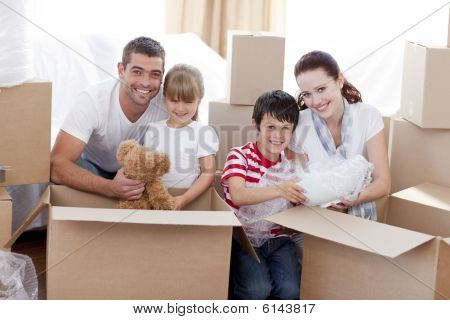 Family Moving Home With Boxes Around