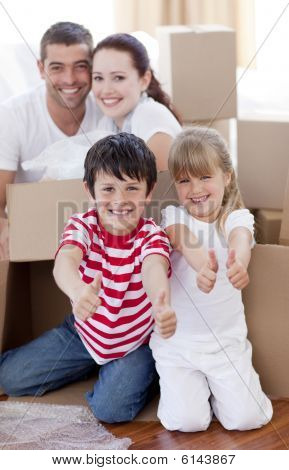 Family Moving House With Boxes And Thumbs Up
