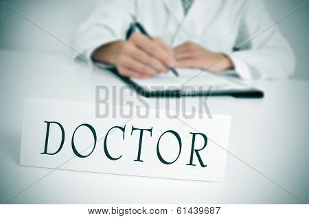 a doctor sitting in the desk of his consulting room writing in a clipboard and a nameplate with the word doctor written in it