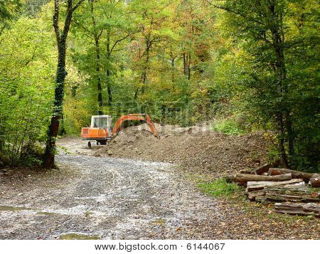 Orange mechanical digger in forest