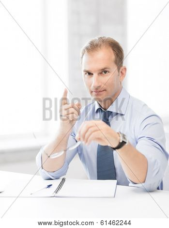 handsome businessman with spectacles showing warning gesture