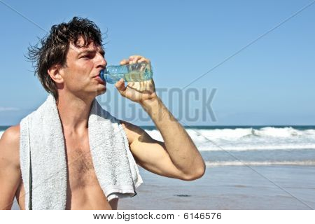 Sportsman drinking water after sporting at the beach