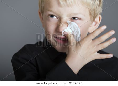 Young Blonde Boy With A Cold And A Tissue